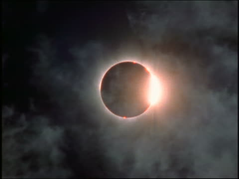 low angle solar eclipse moving past totality with clouds in foreground / Austria 1999