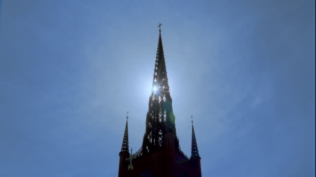 low angle spire of riddarholm church with time lapse clouds + sun in background / stockholm, sweden - spire stock videos & royalty-free footage