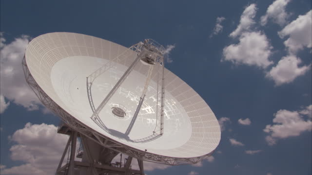 Low Angle static _ Clouds drift over a radio telescope dish / Fort Irwin, California, USA