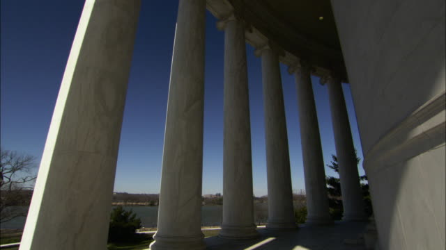 Low Angle static - A blue sky shines through the colonnade of Jefferson Memorial in Washington D.C. / Washington, D.C., USA