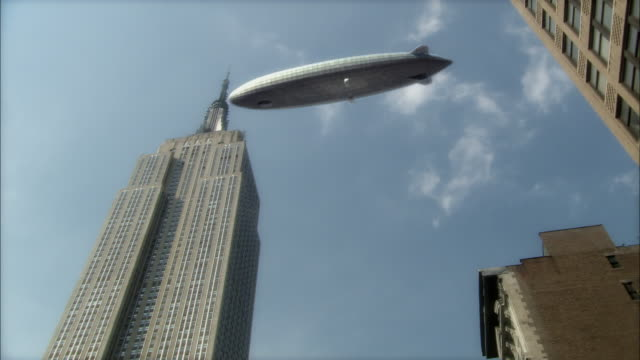 low angle static - a dirigible floats above the empire state building. / new york city, new york, usa - アールデコ点の映像素材/bロール