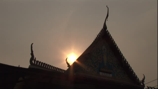 low angle static - a golden sun silhouettes the peaked roof of a buddhist temple. / thailand - sun roof stock videos & royalty-free footage