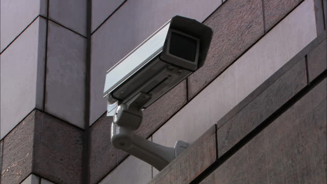 low angle static - a security camera watches from a building's exterior. / london, england - big brother orwellian concept stock videos & royalty-free footage
