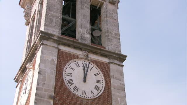 stockvideo's en b-roll-footage met low angle static - bells ring in a clock tower. / varese, italy - klokkentoren met luidende klokken