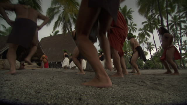 low angle static - hawaiians hula dance to a drumbeat at the place of refuge on hawaii's big island. / hawaii, usa - hawaiianische kultur stock-videos und b-roll-filmmaterial