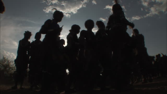 low angle static - silhouetted ethiopian women dance in a circle. / ethiopia - ethiopia stock videos and b-roll footage