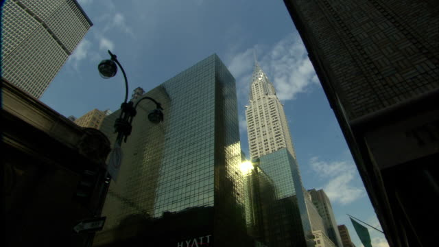 low angle static - the sun glints off the windows of the grand hyatt next to the chrysler building in new york city. / new york city, new york, usa - hyatt stock videos & royalty-free footage