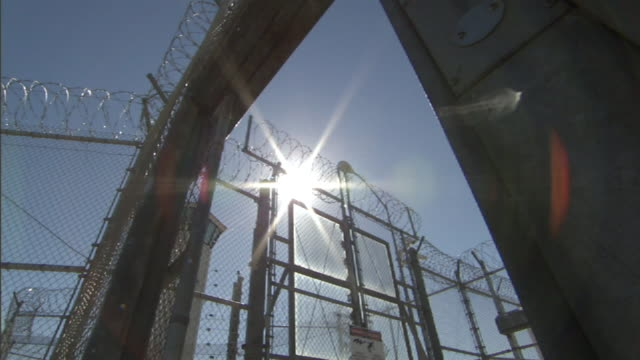 Low Angle static - The sun shines above a closing prison gate. / California, USA