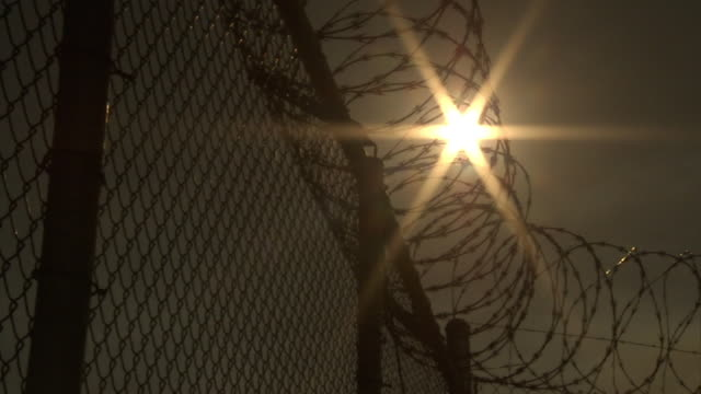 vidéos et rushes de low angle static - the sun shines behind razor wire on top of a fence. / california, usa - clôture