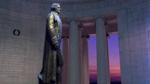 Low angle statue of Jefferson in Jefferson Memorial / time lapse sky darkening in background dusk to night