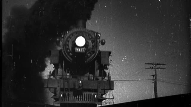 stockvideo's en b-roll-footage met b/w scratched low angle steam train passing over camera on tracks at night - stoomtrein