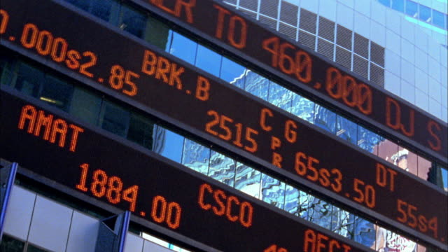 vídeos de stock, filmes e b-roll de low angle stock ticker led displays scrolling on building screens - wall street