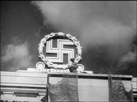 B/W 1945 low angle swastika sculpture on roof of Nuremberg Stadium with soldier nearby / newsreel