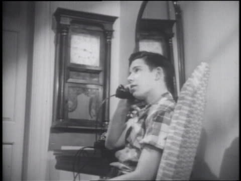 b/w 1953 low angle teen boy sitting in chair + talking on telephone - one teenage boy only stock videos & royalty-free footage