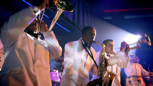 low angle MS three men in brass section performing on stage turning left + right + bending in unison