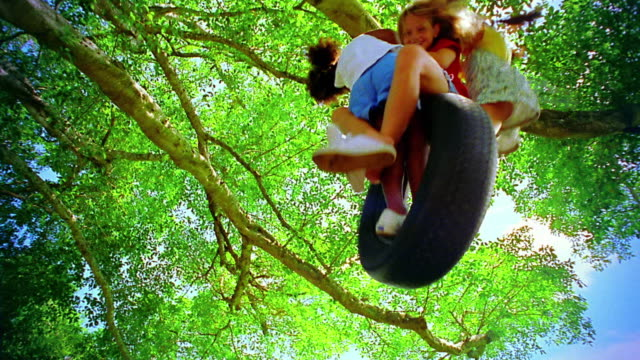 low angle three young girls swinging + spinning on tire swing attached to tree / florida - tyre swing stock videos & royalty-free footage