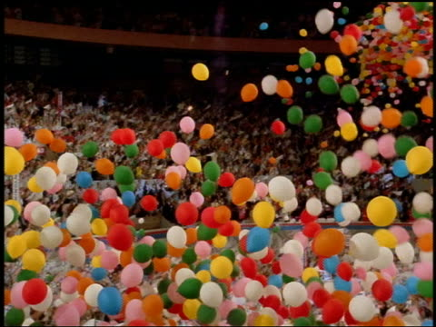 1992 low angle tilt down balloons falling on high angle wide shot pan crowd at Democratic National Convention / New York City