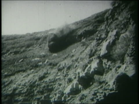 B/W 1939 low angle tilt down car driving off cliff + breaking up as it falls / documentary