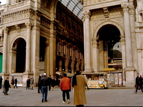 low angle tilt down from archway of galleria vittorio emanuele ii to pedestrians near the entrance of the arcade in the piazza del duomo / tilt up and down again / milan, italy - piazza del duomo milan stock videos and b-roll footage