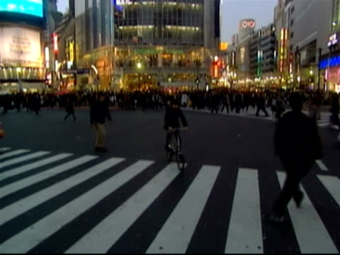 Low angle tilt down from Q Front building to pedestrians crossing the street at Shibuya Crossing / Shibuya Ward, Tokyo, Japan