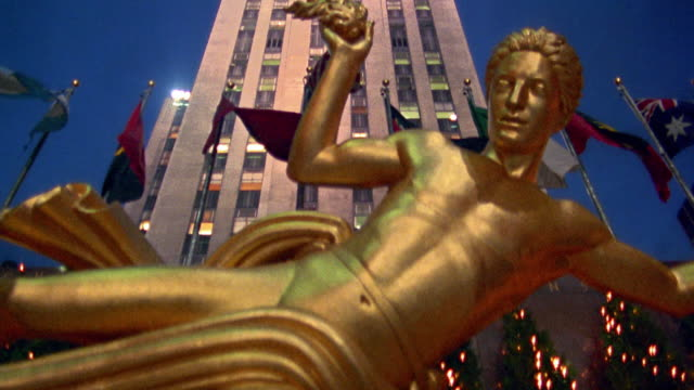 low angle tilt down from rockefeller center to gold prometheus statue in front at night / midtown manhattan, new york city - rockefeller center video stock e b–roll