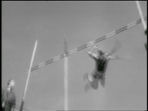 b/w 1933 low angle tilt down man pole vaulting over bar / philadelphia / newsreel - 1933 stock videos & royalty-free footage
