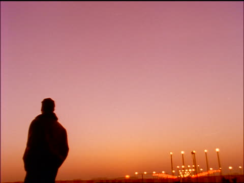 vídeos de stock, filmes e b-roll de rear view low angle tilt down man walking + looking up as airliner comes in for landing at sunset - 1990