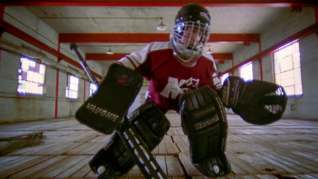 Low angle tilt down tilt up ice hockey goalie with protective gear practicing movements in rink without ice / Nova Scotia
