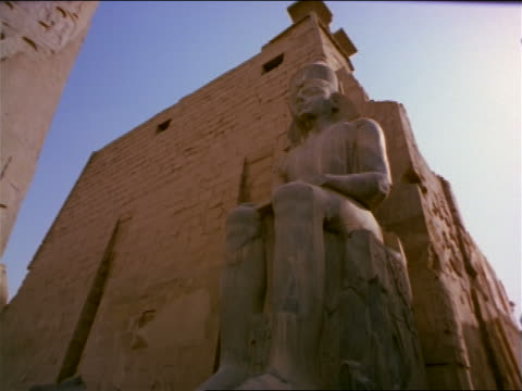 low angle tilt down tilt up obelisk covered in hieroglyphics + large Egyptian statue in ruins / Temple of Luxor