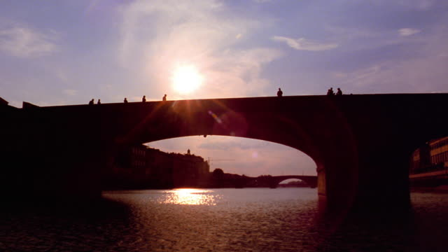 low angle tilt up boat point of view passing under silhouetted bridge over arno river at sunset / florence, italy - florenz italien stock-videos und b-roll-filmmaterial
