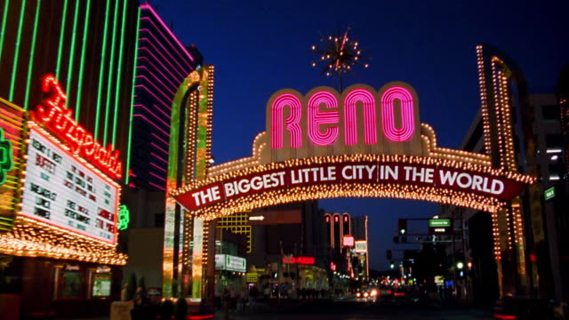low angle tilt up car point of view towards and under neon reno sign at night / nevada - nevada stock videos & royalty-free footage