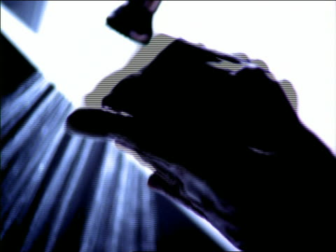 Low angle tilt up close up silhouette of male hands scrubbing fingers with brush / water running in background