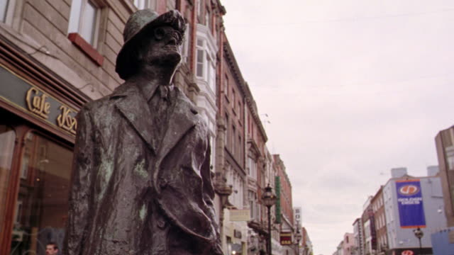 low angle tilt up PAN from Grafton Street to bronze statue of James Joyce / Dublin, Ireland