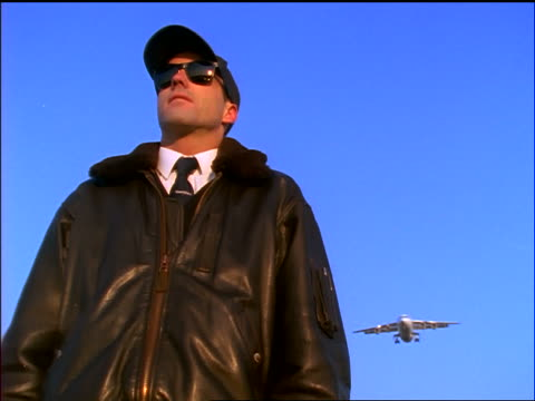 vidéos et rushes de low angle tilt up man in black leather jacket + sunglasses looking up as airliner flies overhead - casquette de baseball