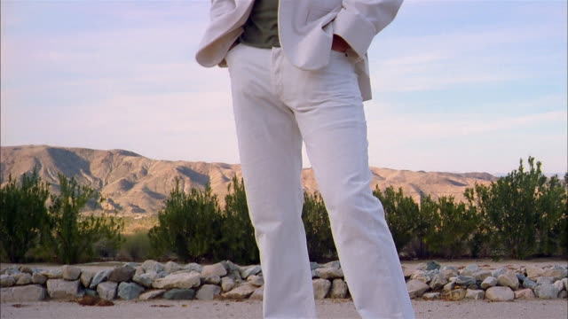 low angle tilt up man wearing white suit in desert w/mountains in background - 2000s style点の映像素材/bロール
