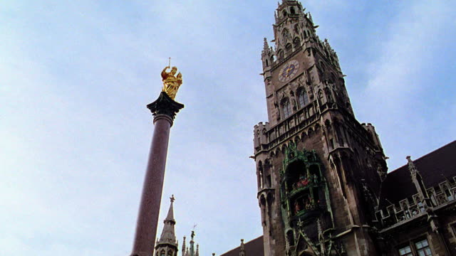 vidéos et rushes de low angle pan tilt up neues rathaus + mariensaule / tilt down tilt up marienplatz with crowd / munich, germany - rathaus