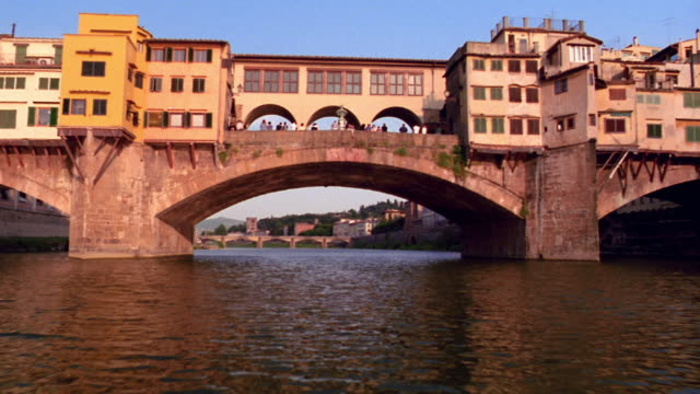 low angle pan tilt up tilt down boat point of view passing under ponte vecchio on arno river / florence, italy - florenz italien stock-videos und b-roll-filmmaterial