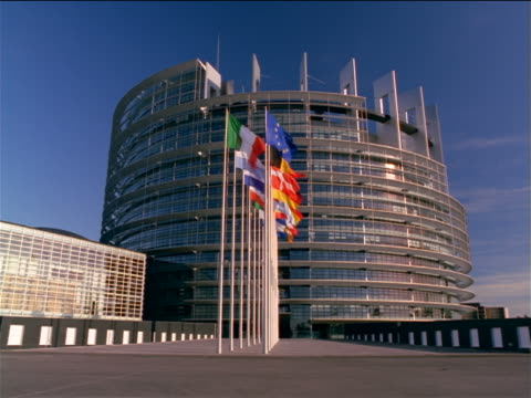 vidéos et rushes de low angle tilt up tilt down pan louise weiss eu parliament building with flags in front / strasbourg, france - arbitre