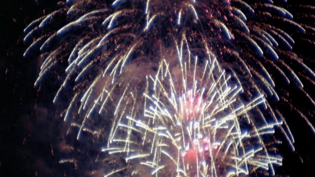 Low angle tilt up tilt down pan several fireworks explosions in night sky / New Orleans, Louisiana