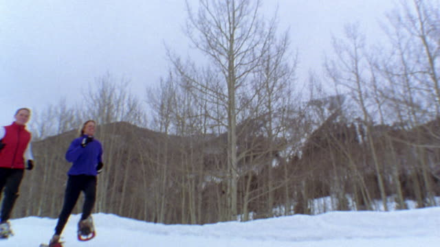 Low angle tilt up two women running in snowshoes w/bare trees in background / Vail, Colorado, USA