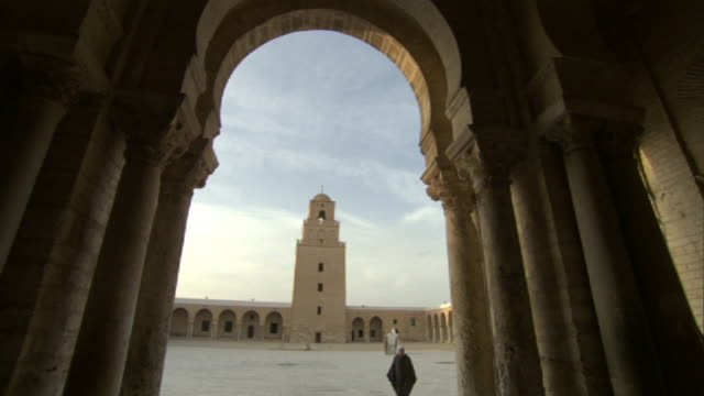 low angle tilt-down - a robed man walks across the courtyard of a mosque in tunisia. / tunisia - tunisia stock videos & royalty-free footage
