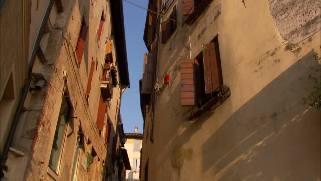 Low Angle tilt-down - Close, old buildings form a narrow alley. / Asolo, Italy
