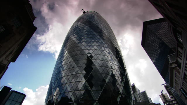 low angle tilt-up - clouds drift above the gherkin and other modern skyscrapers in london. / london, england - swiss re stock videos & royalty-free footage