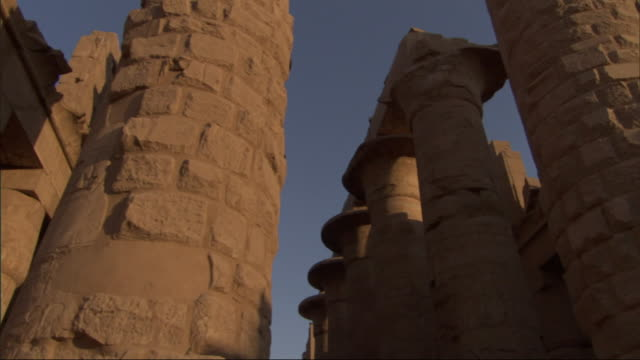 Low Angle, tilt-up tracking-left - Spires of old adobe buildings stand against a clear blue sky / Egypt