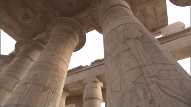 Low Angle, tilt-up tracking-right - Drawings and hieroglyphics cover columns at the ruins of an ancient Egyptian building