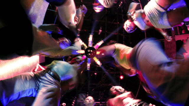 fisheye low angle time lapse circle of people dancing around camera on floor in nightclub with flashing lights - surrounding stock videos and b-roll footage