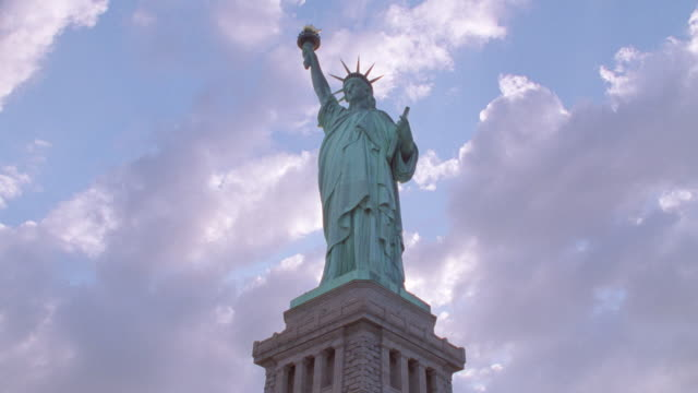 low angle time lapse clouds in blue sky above statue of liberty / nyc - freiheitsstatue stock-videos und b-roll-filmmaterial