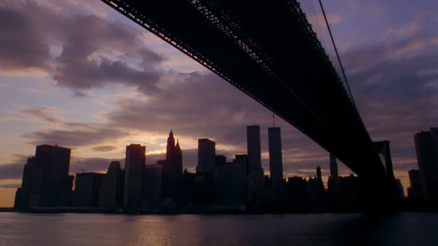 low angle time lapse clouds moving and sun setting behind brooklyn bridge with boats in foreground + skyline in background / nyc - world trade centre manhattan stock videos and b-roll footage