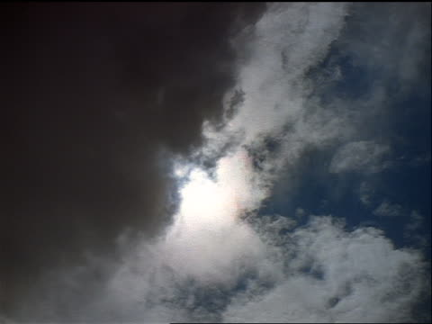 low angle time lapse complete solar eclipse with clouds in foreground
