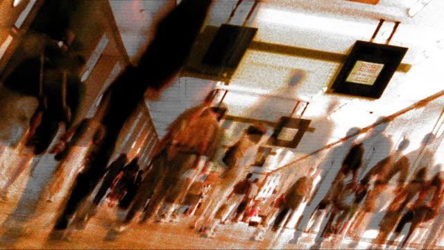 vidéos et rushes de grainy anamorphic cross process low angle time lapse crowds walking indoors with tv monitors hanging from ceiling - procédé croisé